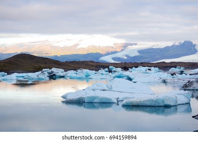 Melting icebergs in the Jökulsárlón lagoon in Iceland, summer. Glacier, mountain and clouds in the background. Representation of global warming and climate change.