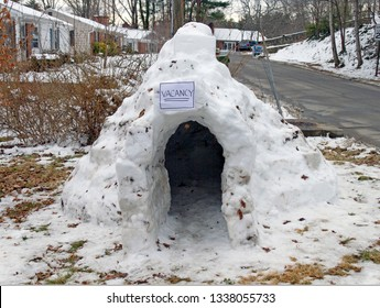 A melting, lopsided igloo displays a humorous vacancy sign at winter's end