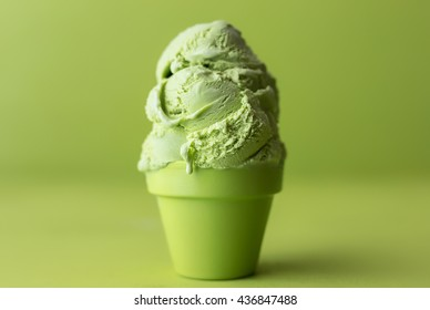 Melting matcha green tea ice cream on a lime green background.