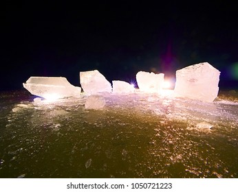 Melting pieces of chopped ice blocks. Strong colorful backlight shine deep cracks, low angle view. Far flat horizon.