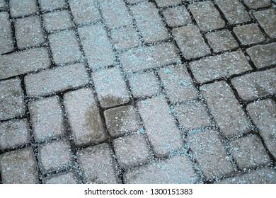 Melting salt on the sidewalk in winter season
