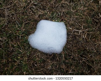 melting snow and ice on green and brown grass
