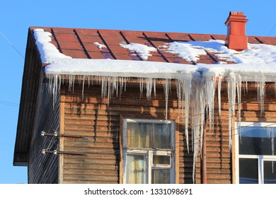 Melting snow and icicles hanging on the roof of a wooden house against blue sky in early spring