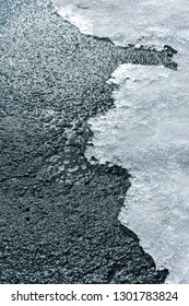 melting snow on edge of asphalt road in spring season