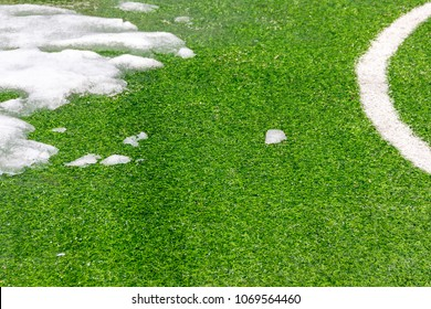Melting snow on a football field. Close-up
