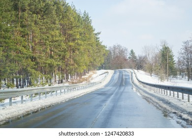 Melting snow outside of the city on the country road. Weather forecast for early spring. Melting snow, difficult road. Early spring in temperate climate. Spring is coming. Sunny spring weather