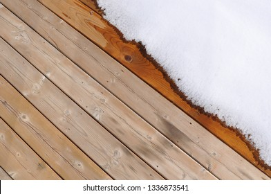 Melting snow over plank of  wooden floor in the deck of the house