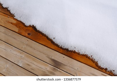 Melting snow over plank of  wooden floor