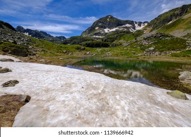 Melting snow, pond and peaks in the french Pyrenees mountains, Ariege in France