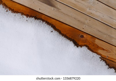 Melting snow in wooden floor of the deck