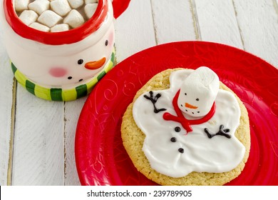 Melting snowman sugar cookie sitting on red plate with snowman mug filled with hot chocolate and marshmallows