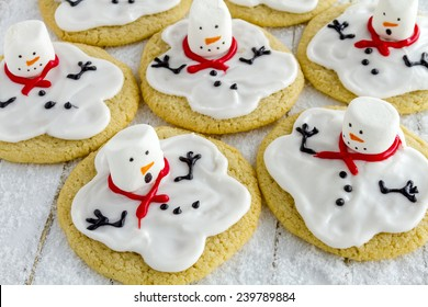 Melting snowman sugar cookies sitting on white wooden table with sparkling sugar snow
