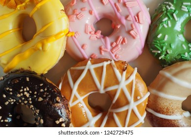 Melting sweet sugary coating doughnuts arranged in the paper box packaging. Typically the trans fat in donuts theme, Food in take out container or to go packaging concept. (close up, selective focus)