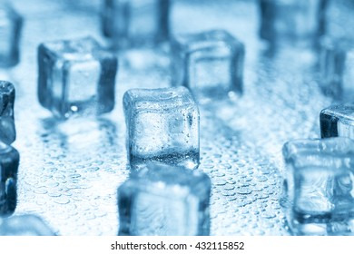 Melting transparent blue ice cubes on glass