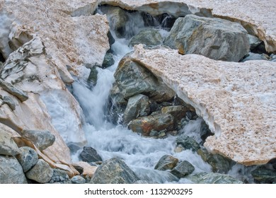 Meltwater stream at ablation zone of Sofia glacier running through the stones and surrounded by brown melting snow at the top of Arkhyz mountains, Karachay-Cherkessia, Russia