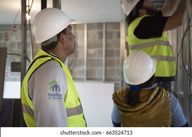 A member from Habitat for Humanity New York City works with volunteers on a home building construction project in the Brownsville section of Brooklyn during Fleet Week New York - NEW YORK MAY 25 2017.