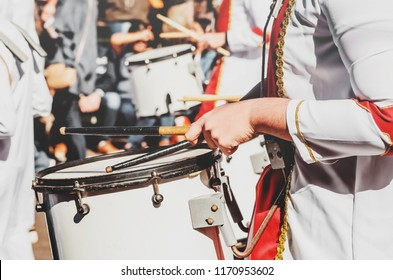 Member of a military fanfare playing a mobile bass drum. Playing a mobile bass drum with drumsticks. Bass drum attached to the body, musician walking and playing on a parade.
