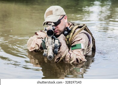 Member of Navy SEAL Team crossing the river with weapons