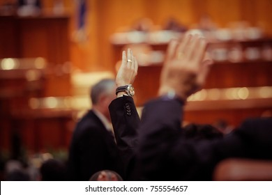 Member of Romanian Parliament is voting by raising his hand