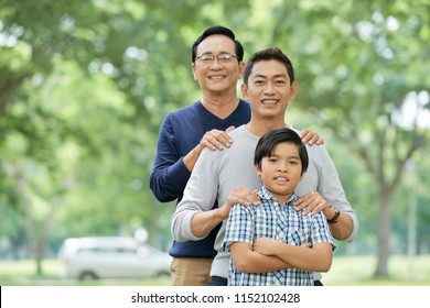 Threemale members of Asian family smiling and looking at camera while standing on blurred background of park