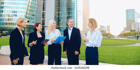 Members of business organization talking outside and smiling with document case and tablet in hands. Concept of walking biz team and resting outside. Group people dressed in suits and white shirts