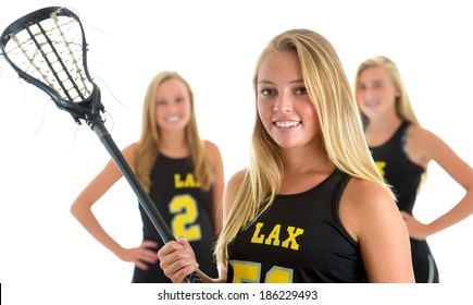 Members of a girls lacrosse team. Focus on woman in front, teammates soft focused in background. Studio shot, isolated on white background.