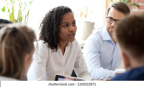 Members of international company gathered together in office boardroom for brainstorming or briefing before workday. Mixed race african team leader sharing ideas with coworkers caucasian colleagues