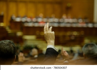 Members of Romanian Parliament voting by raising their hands