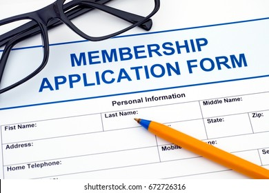 Membership application form with ballpoint pen and glasses.
