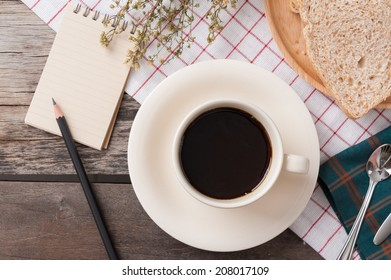 Memo pad with bread and a cup of coffee on table.