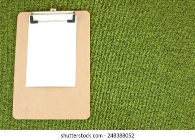 Memo Pad brown corrugated pattern on green carpet.
