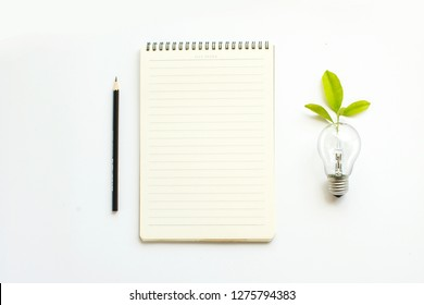 Memo pad and light bulb icon with growing plant on white table top. Conceptual brainstorming image.