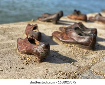 memorail monument - Old metal rusty shoes on parapet of Danube river bank embankment. Monument to the victims of Nazi repression. Budapest, Hungary