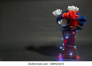 Memorial day flowers with black background and lights around the vase