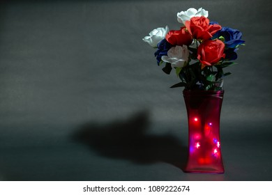Memorial day flowers with black background and light inside the vase