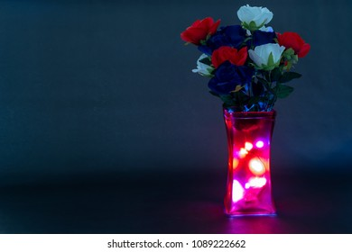 Memorial day flowers with dark blue background and lights inside the vase
