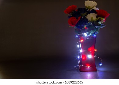 Memorial day flowers on dark background and lights around the vase