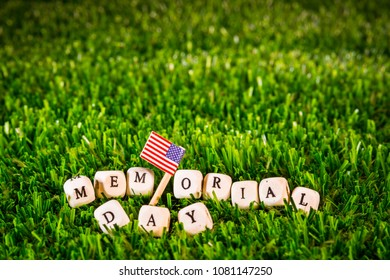 memorial day phrase formed by wooden letters and USA flag over green grass.