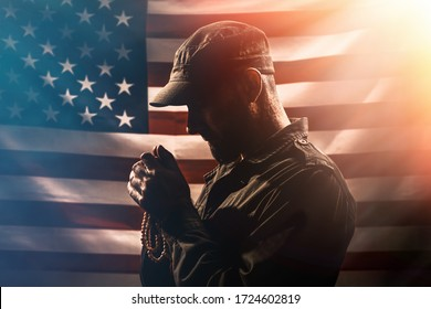 Memorial day, veterans day. Portrait of a Soldier holding a rosary and praying. American flag on the background. Copy space. Concept of American holidays and religion.