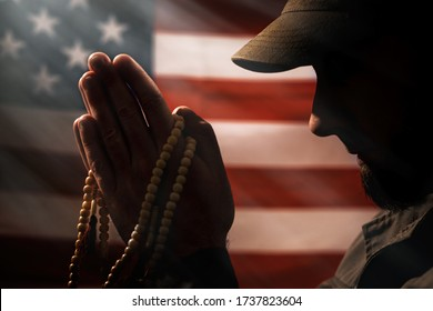 Memorial day, veterans day. A soldier holds a rosary in his hands and prays holding it to his face. Close up. American flag on the background. Concept of American holidays and religion