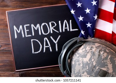 Memorial day weekend text on black chalkboard, USA flag background. US Army kevlar combat helmet camo cover, tactical goggles. Stars & stripes veteran remembrance symbol. Close up, copy space top view
