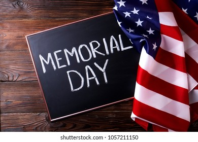 Memorial day weekend text written on wooden black chalkboard with USA flag. United States of America stars & stripes patriot veteran remembrance symbol. Background, close up, copy space, top view.