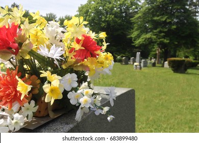 A memorial display of flowers on top of a headstone after a funeral. Additional tombstones in the distance.