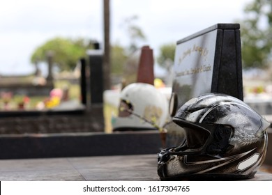 A memorial grave site of two motorcycle riders that lost their lives to an accident on a bike. Helmets set on a grave site to remember the loss of loved ones and friends to a bike accident.