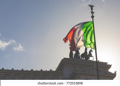 Memorial monument the Vittoriano or Altar of the Fatherland, in Venezia square, with waving italian flag. Italian and Rome patriotic symbols, located on the Campidoglio hill in Rome.