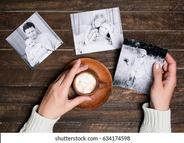 Memories concept. Family photos and cup of coffee or cocoa in female hands on wooden background. Top view.
