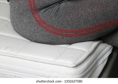 A memory foam mattress with a seated young lady on it