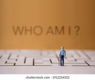 Memory Loss from Dementia, Parkinson or Alzheimer Disease Concept. Brain Function Decline. Miniature of a Senior Elderly Man standing in front of the Maze and the Question of Who am i