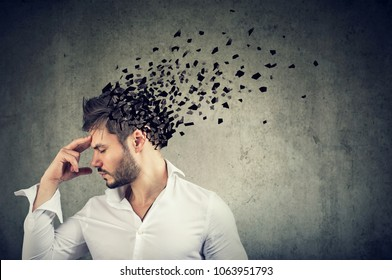 Memory loss due to dementia or brain damage. Side profile of a man losing parts of head as symbol of decreased mind function.