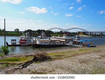 MEMPHIS, TENNESSEE - JULY 23, 2019: Old riversboats and some removed paddlewheels next to the shore of the Mississippi river with the Hernando de Soto Bridge in Memphis, TN in the background.